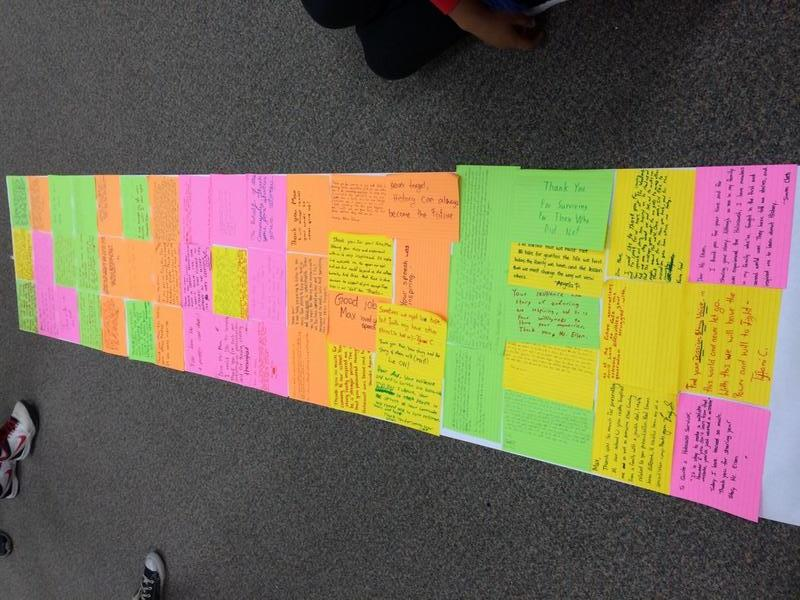 Students collect individual reflections following a survivor testimony to form a banner